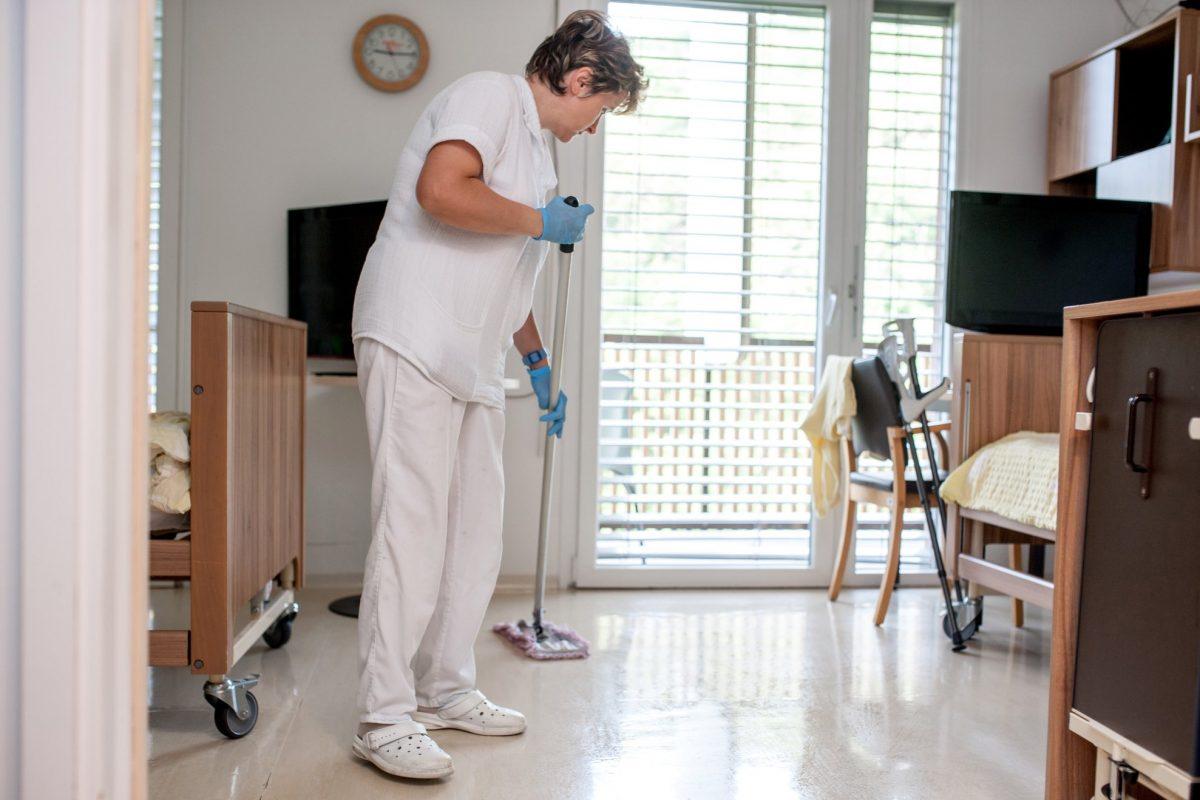 Medarbejder gør rent i en plejebolig